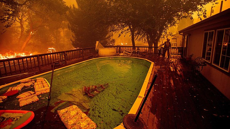 A firefighter gathers water from a pool while battling the Ranch Fire