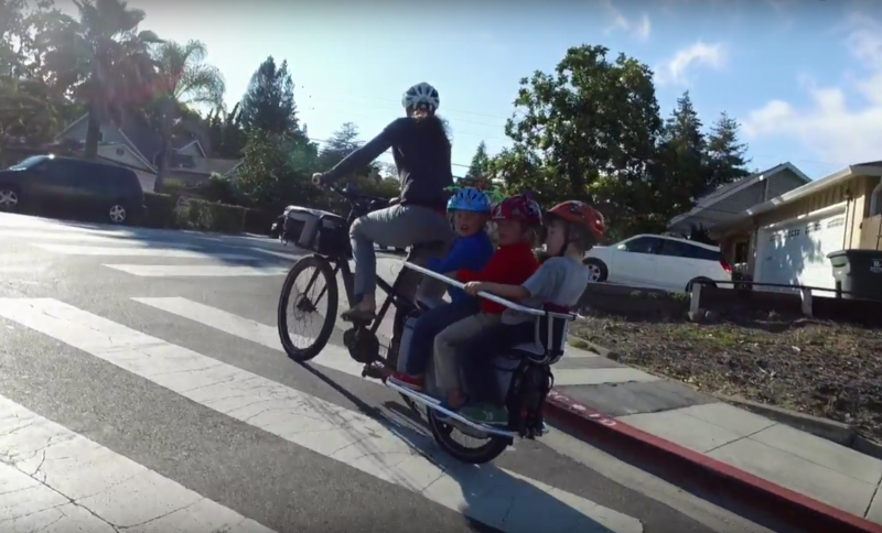 Woman riding uphill with cargo bike and three kids on back