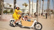 Woman riding Yuba cargo bike with kids in cargo box