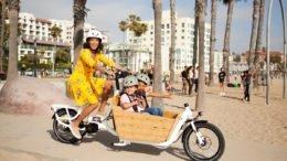 Woman riding Yuba cargo bike with kids in cargo box