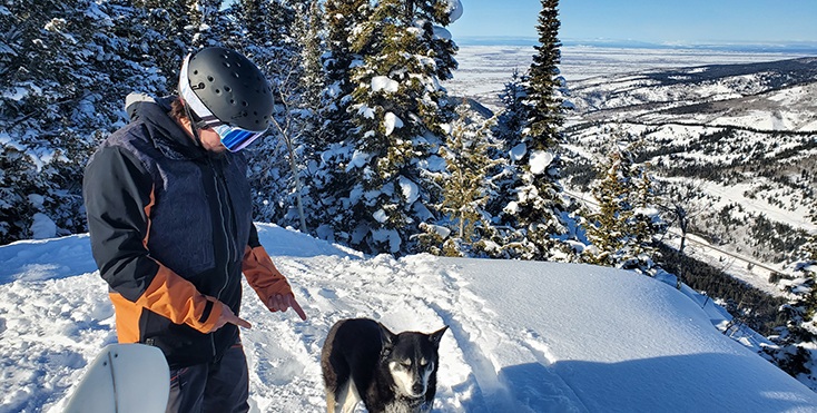 Snowboarder with a Dog in the Backcountry