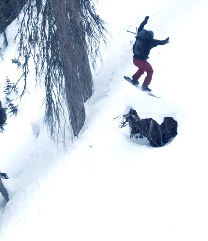 Snowboarder Spinning off Cliff Jump
